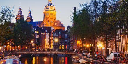 Njut av kvällsliv vid kanalerna i Amsterdam, Holland.