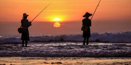 Fiskare i solnedgången i Jimbaran, Bali.