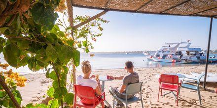 Njut av utsikterna över stranden, Röda havet och båtarna.