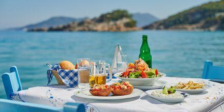 Njut av en god grekisk lunch vid vattnet.