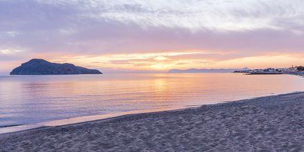 Solnedgång på stranden vid hotell Porto Platanias Luxury Selection.
