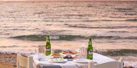 Middag på stranden i solnedgången i Psalidi på Kos, Grekland.