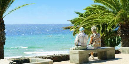 Njut av utsikten längs strandpromenaden i Puerto del Carmen, Lanzarote.