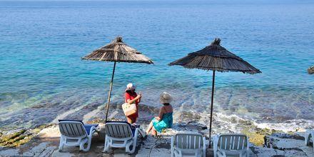 Det finns både stränder och berghällar att bada från i det kristallklara vattnet i Saranda, Albanien.