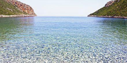 Kristallklart vatten och stenstrand i Vlychada, Santorini.